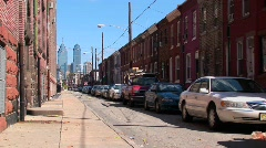 Vehicles are parked along a street of brick buildings in Stock Footage