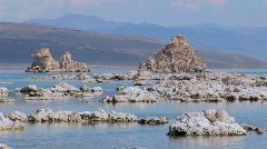Clouds are above tufa formations sitting in water while mountains - stock footage
