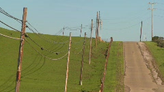 A country road moves along beside green fields Stock Footage