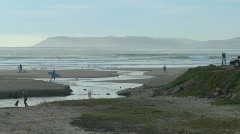 A surfer walks across an estuary along the Central California coast Stock Footage
