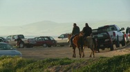 People ride horses along a beachside parking lot in California Stock Footage
