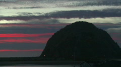 A time lapse shot over a dark round mountain at Morro Bay, California Stock Footage