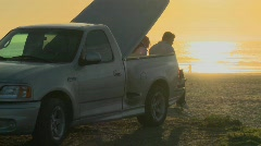 A couple sits on the flatbed of a pickup truck in California shot Stock Footage