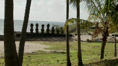 Easter Island statues stand in a long row on a distant beach Stock Footage