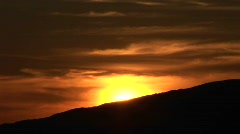 A golden sun sinks behind a silhouetted mountain Stock Footage