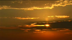 A golden sun peeks through a bank of clouds Stock Footage