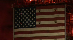 An American flag mural decorates the side of an oil refinery at night Stock Footage