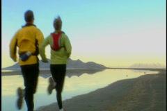 Couple jog into desert sunrise - stock footage