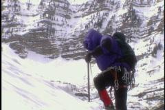 Mountain climber ascends mountain - stock footage