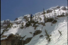 Skier skis over cliff jump - stock footage
