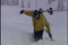 Skier carries skis up powdery hill Stock Footage