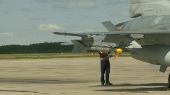 Military, F16 Falcon fighter jet ground crew with jet takeoff in bg Stock Footage