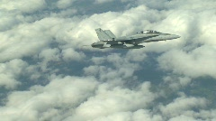 military, F18 Hornet fighter jet banking partial zoom in, clouds in bg - stock footage
