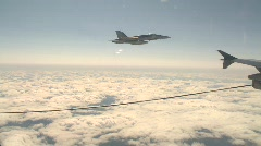 military aerial, F18 Hornet fighter jet in flight above clouds with fuel drogue - stock footage