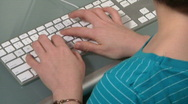 Woman types on computer Stock Footage