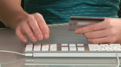 Young woman enters credit card on computer Stock Footage
