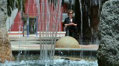 Woman on phone through fountain Stock Footage