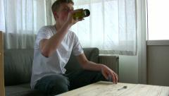 Older teenager drinks a beer - stock footage