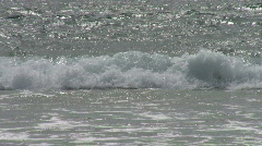 Breaking ocean wave shown on a sunny day with foam in the foreground Stock Footage