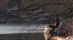 Two women on a rock in a pond in Central Park Stock Footage