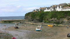 Fishing boats moored at low tide in Port Isaac harbour in Cornwall England. Stock Footage