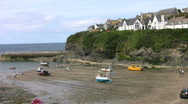 Stock Video Footage of Fishing boats moored at low tide in Port Isaac harbour in Cornwall England.