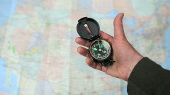 Hand Holds Spinning Compass Over Out of Focus Map Stock Footage