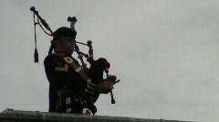 rooftop piper with salute at end - stock footage