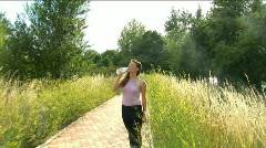 Girl drinks water after playing sports Stock Footage