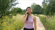 Stock Video Footage of Girl goes on a footpath and speaks by phone