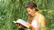 Stock Video Footage of Girl reads the book on the bank of river
