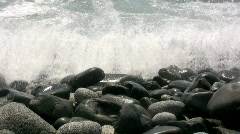Black rocks on the beach Stock Footage