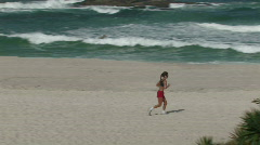 Ocean beach jogger 1 Stock Footage