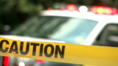 Caution Tape at an Accident Scene with Police Vehicle Behind - stock footage