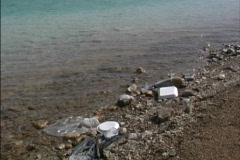 Environmental Issues Trash by lake shore - stock footage