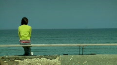 Young woman sitting and looking at the ocean 1 Stock Footage