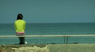 Stock Video Footage of Young woman sitting and looking at the ocean 1