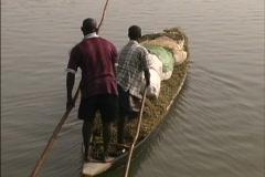 Boys polin a  loaded canoe in Senegal Stock Footage