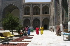 Women in madrassa courtyard Samarkand Stock Footage