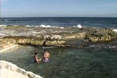 Couple in seaside tidal pool in Yucatan Stock Footage