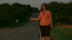 Girl walking down road hitch hiking Stock Footage