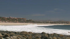 Rolling waves crashing against undertow in Baja Mexico. Hotels in background - stock footage