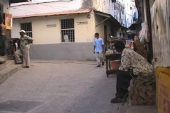 People sitting in front of a shop in Stonetown on Zanzibar island - stock footage