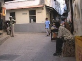 Stock Video Footage of People sitting in front of a shop in Stonetown on Zanzibar island