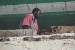 Men working on a boat at the beach on Zanzibar island Stock Footage