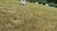 Little girl plays a lawn Stock Footage