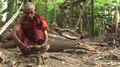 Monk chopping wood in Mandalay, Burma Myanmar Stock Footage