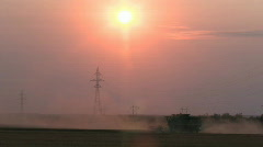 Harvesting combine thrashing wheat on Canadian prairies. Sunset in background Stock Footage