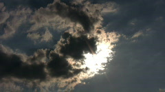 Sun peaks out from behind a dark cloud Stock Footage