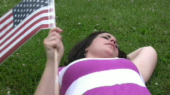 Girl laying in grass waving flag Stock Footage